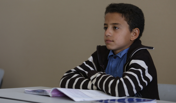 Student Mohammad N., 10, sits at his desk. (Photo: DCIP / Majdi al-Sharif)