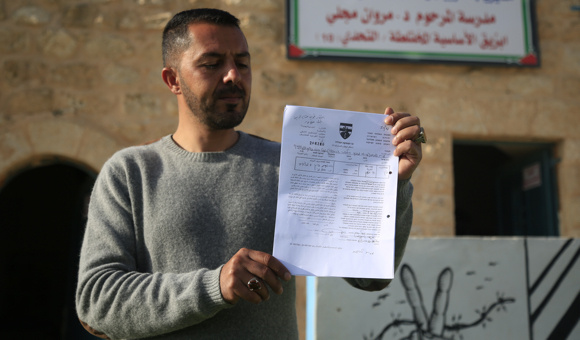 The school's principal, Firas Daraghmeh, holds up a demolition order. (Photo: DCIP / Majdi al-Sharif)