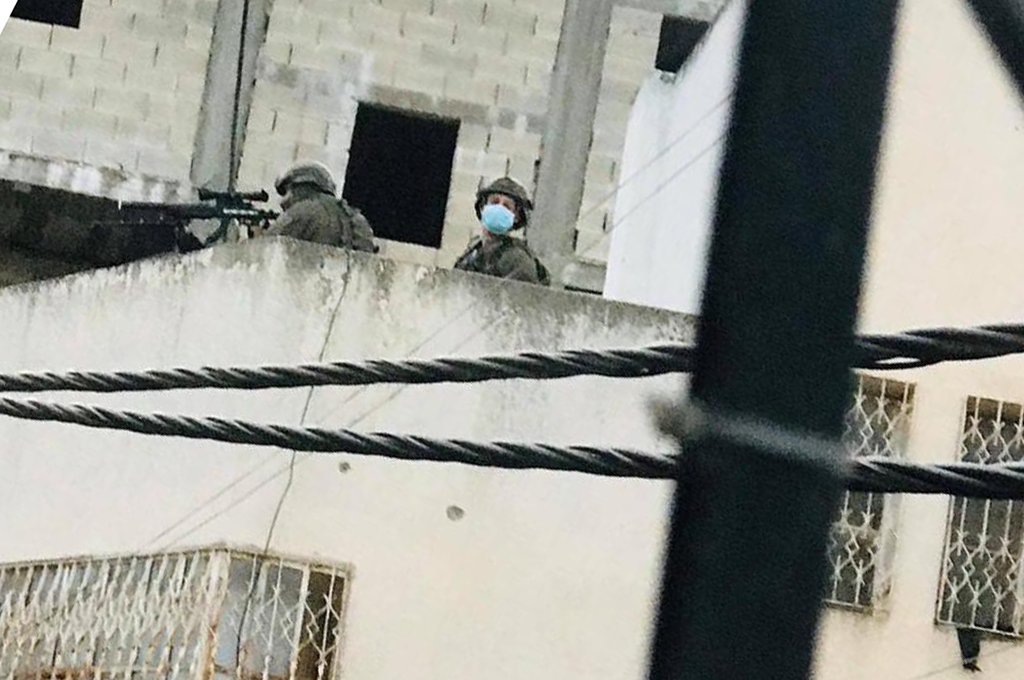 Israeli soldiers deploy on a rooftop in Al-Fawwar refugee camp during a military raid on May 13, 2020.