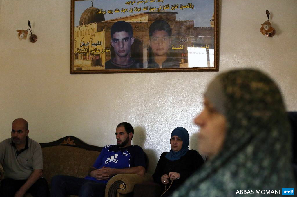The Kasba family sits under portraits of Samer, left, and Yasser who were killed by Israeli forces in 2002 and 2001, at their home in the Qalandia refugee camp near the West Bank city of Ramallah on July 13, 2015. (Photo: AFP / Abbas Momani )