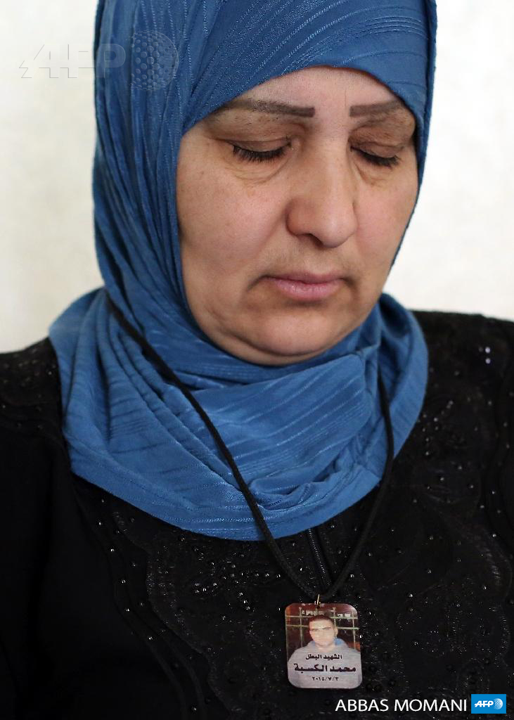 Umm Thaer, mother of Yasser, Samer, and Mohammad Kasba, wears a necklace bearing Mohammad's photo as she sits at her home in Qalandia refugee camp on July 13, 2015. (Photo: AFP / Abbas Momani)