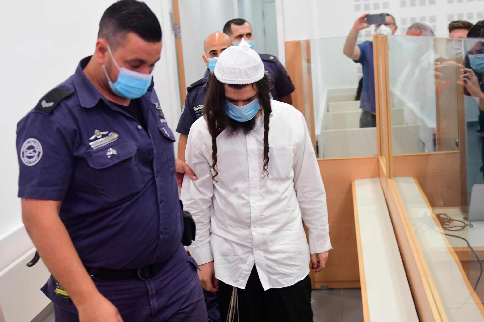 Amiram Ben-Uliel, a Jewish settler, is lead by police into court at the Central Lod District Court, in the central Israeli city on May 18, 2020, for his sentencing hearing over the 2015 arson attack that killed a Palestinian toddler and his parents. (Photo: Avshalom Sassoni)