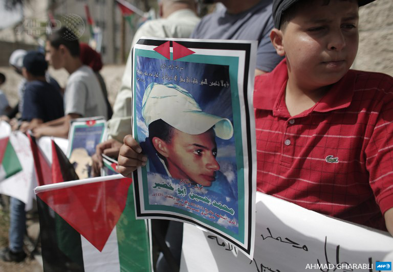 Palestinians hold placards on June 8, 2015, during a demonstration outside the District Court in Jerusalem in support of the family of Mohammed Abu Khdeir (portrait), as the suspects in the killing went on trial. (Photo: AFP / Ahmad Gharabli)