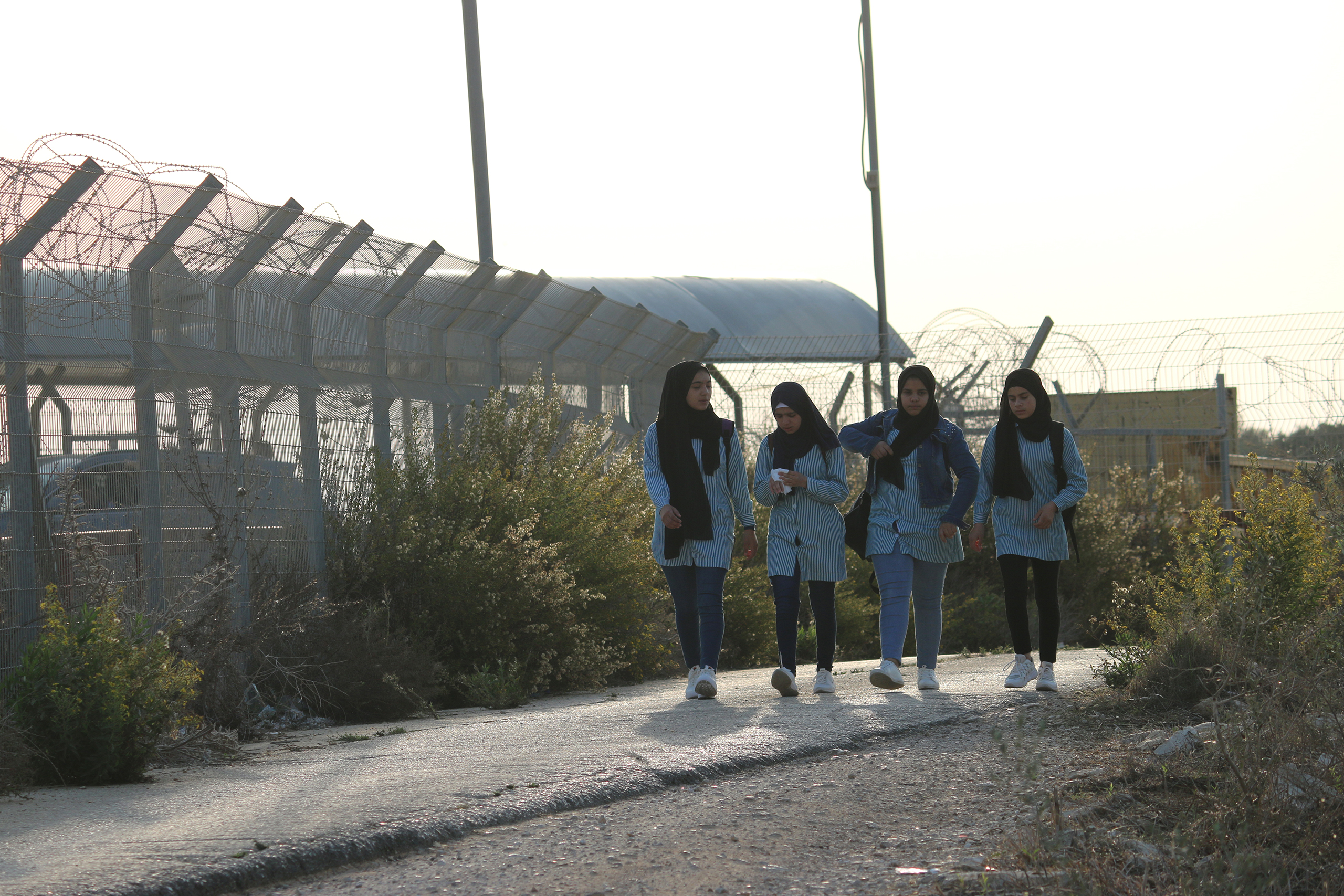 Palestinian students from Dahr Al-Maleh walk toward their school in Tura Al-Gharbiya village after crossing the Israeli military checkpoint on November 07, 2019. (Photo: DCIP / Ahmad Al-Bazz)