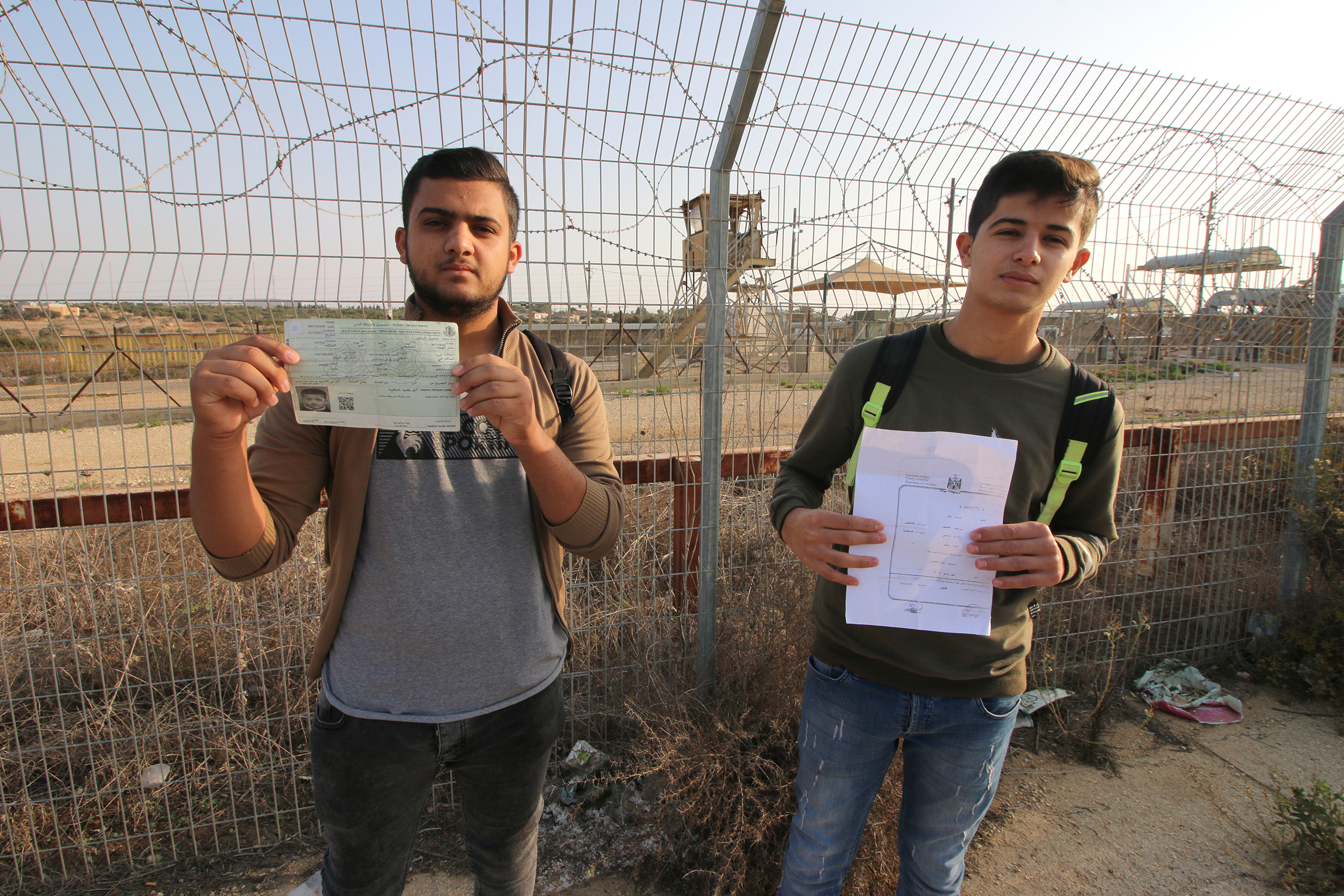 Palestinian students show a military permit (left) and a birth certificate (right) on November 07, 2019 at the Israeli military checkpoint near Tura. The documents are needed to cross the Israeli military checkpoint every morning on their way to school in Tura Al-Gharbiya village. (Photo: DCIP / Ahmad Al-Bazz)