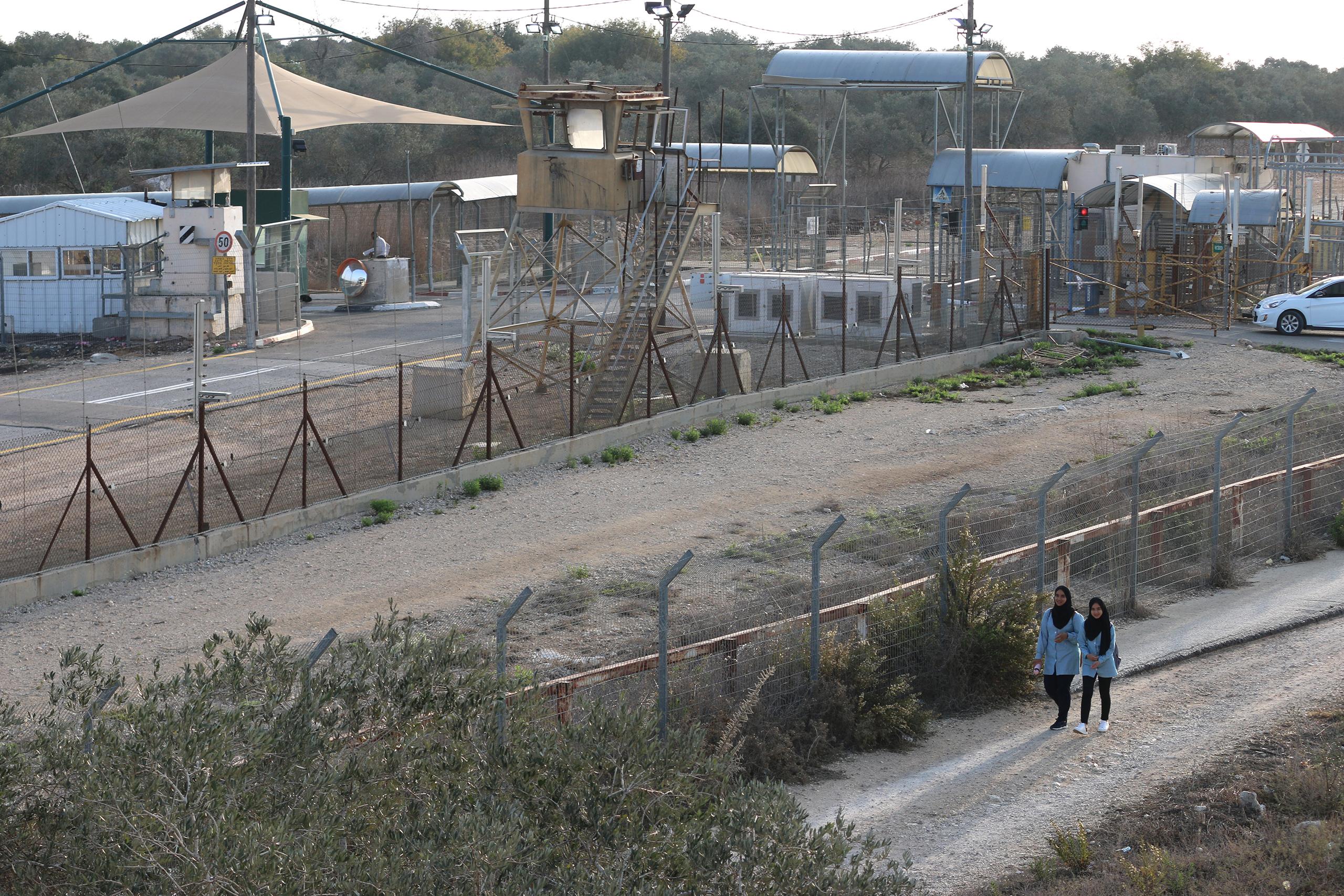 Palestinian students from Dahr Al-Maleh walk next to the Israeli military checkpoint near Tura on their way to school in Tura Al-Gharbiya village on November 07, 2019. (Photo: DCIP / Ahmad Al-Bazz)
