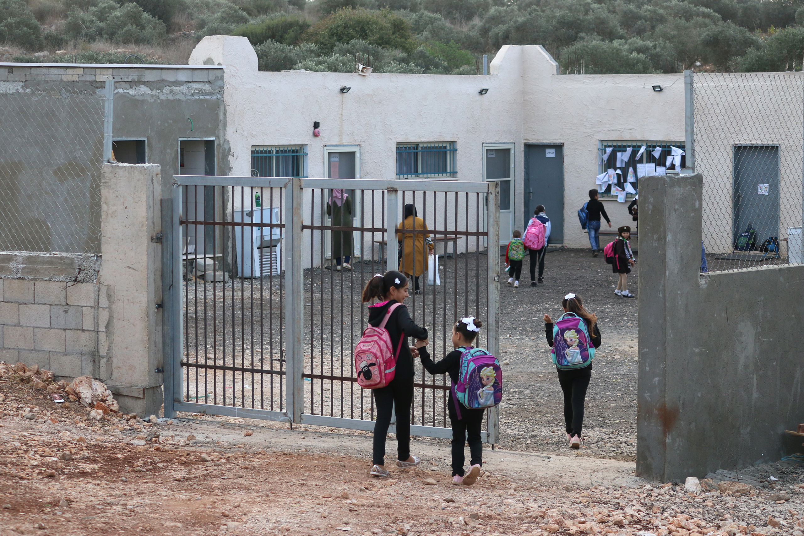 Palestinian students enter their school in Dahr Al-Maleh on November 10, 2019, which is under threat of demolition by the Israeli military. The elementary school was established so younger students in the village could avoid the daily journey through the Israeli military checkpoint to reach neighboring Tura Al-Gharbiya village. (Photo: DCIP / Ahmad Al-Bazz)