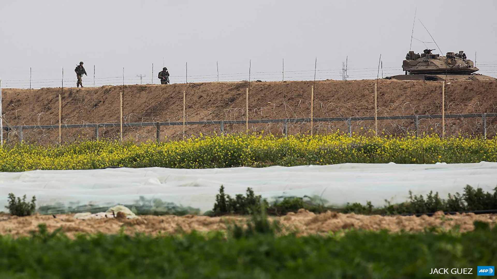 Israeli soldiers walk behind a tank along the Gaza perimeter fence east of Khan Yunis in the southern Gaza Strip on February 23, 2020. (Photo by AFP / Said Khatib)