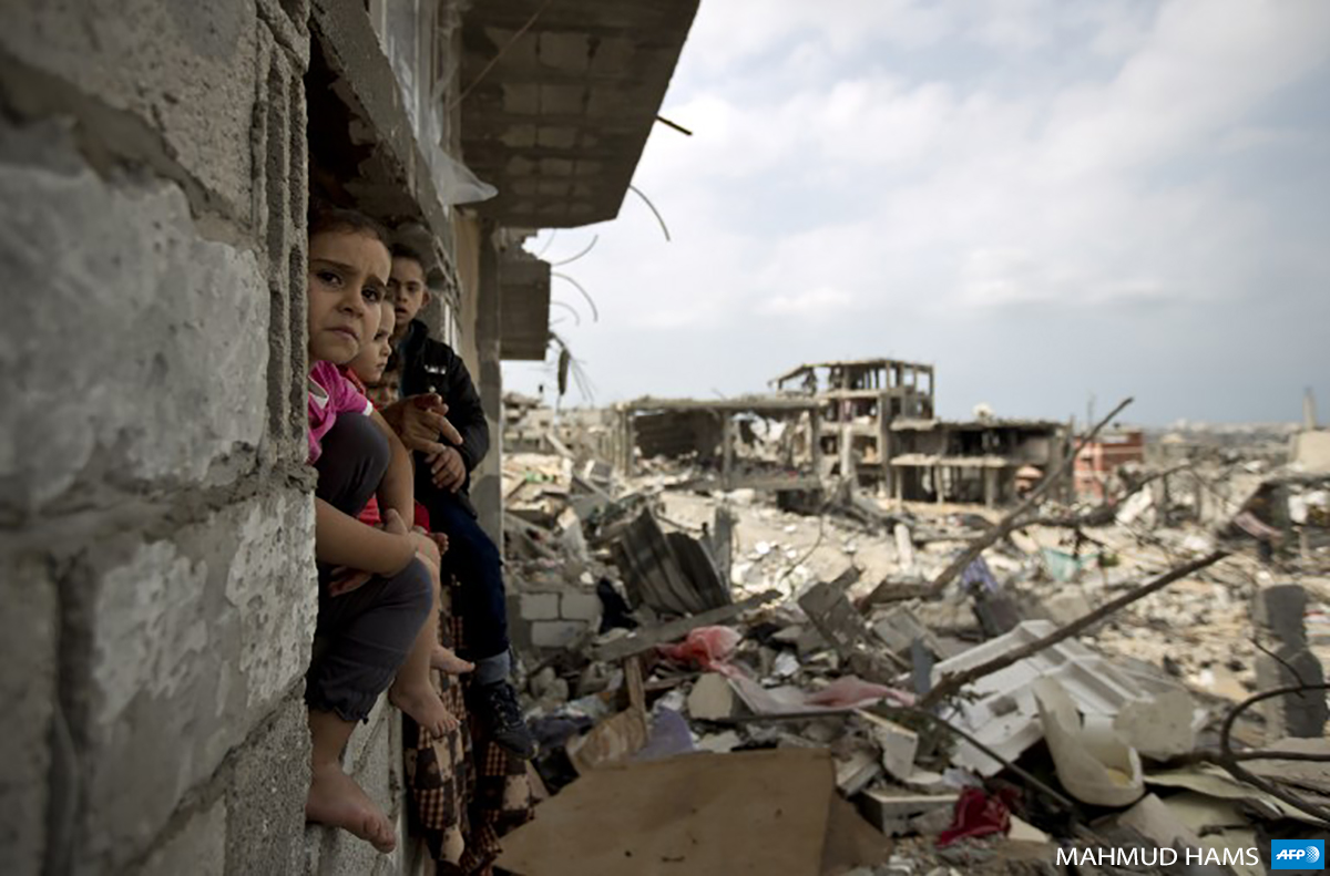 Palestinian children sit on the window of a partially destroyed building in Gaza's al-Tuffah neighborhood, east of Gaza City on October 11, 2014. (Photo: AFP / Mahmud Hams)