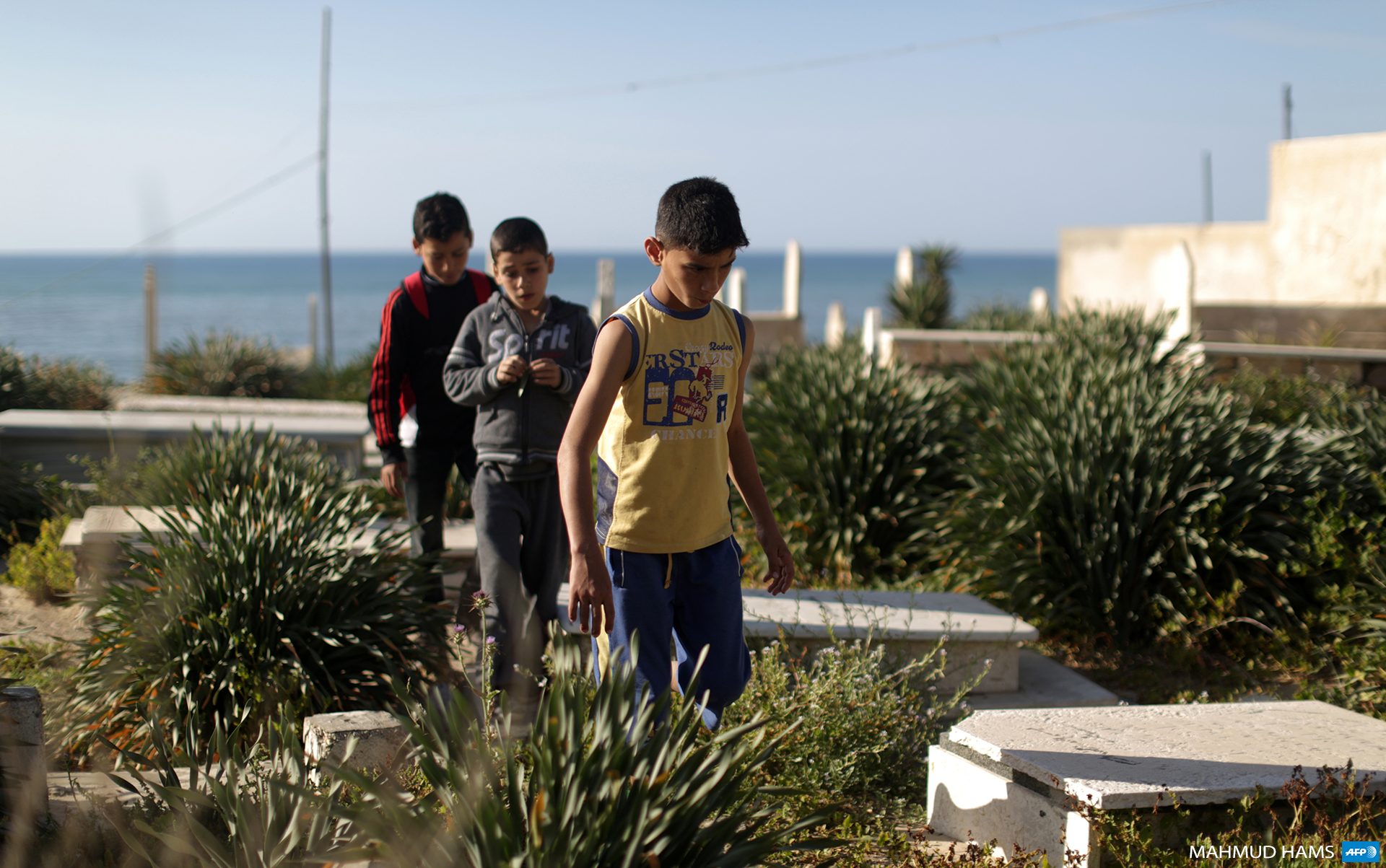 Palestinian boys from the Bakr family, who survived an Israeli military strike on a beach in Gaza that killed four of their relatives during the 50-day Israeli military offensive in the summer of 2014, visit the graves of their loved-ones in Gaza City on March 31, 2015. (Photo: AFP / Mahmud Hams)