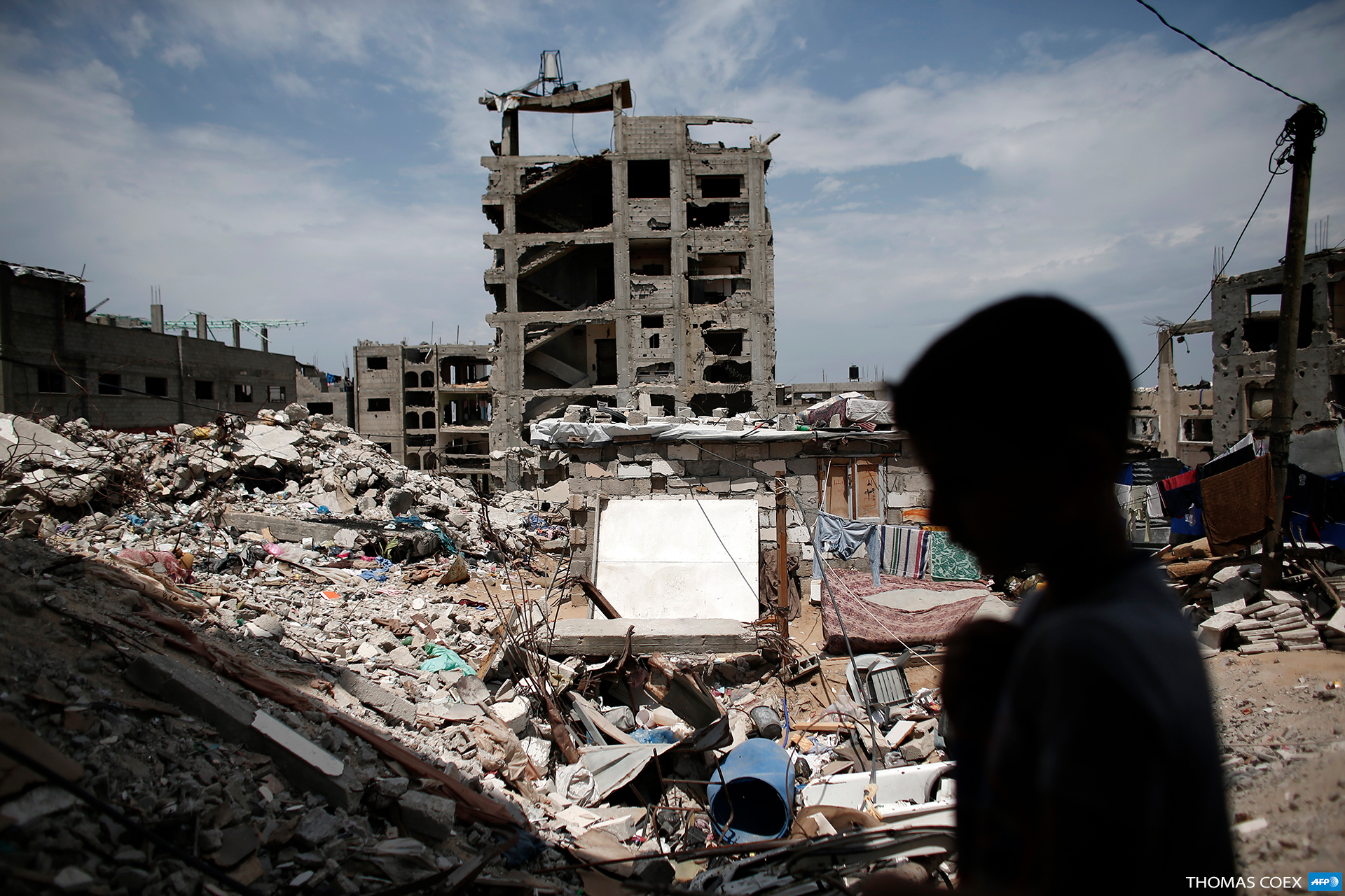 A Palestinian boy walks past his partially rebuilt home over the rubble of his familiy's former house, on May 11, 2015, which was destroyed during the 50-day Israeli military offensive in the summer of 2014, in Gaza's Shuja'iyya neighborhood. (Photo: AFP / Thomas Coex)