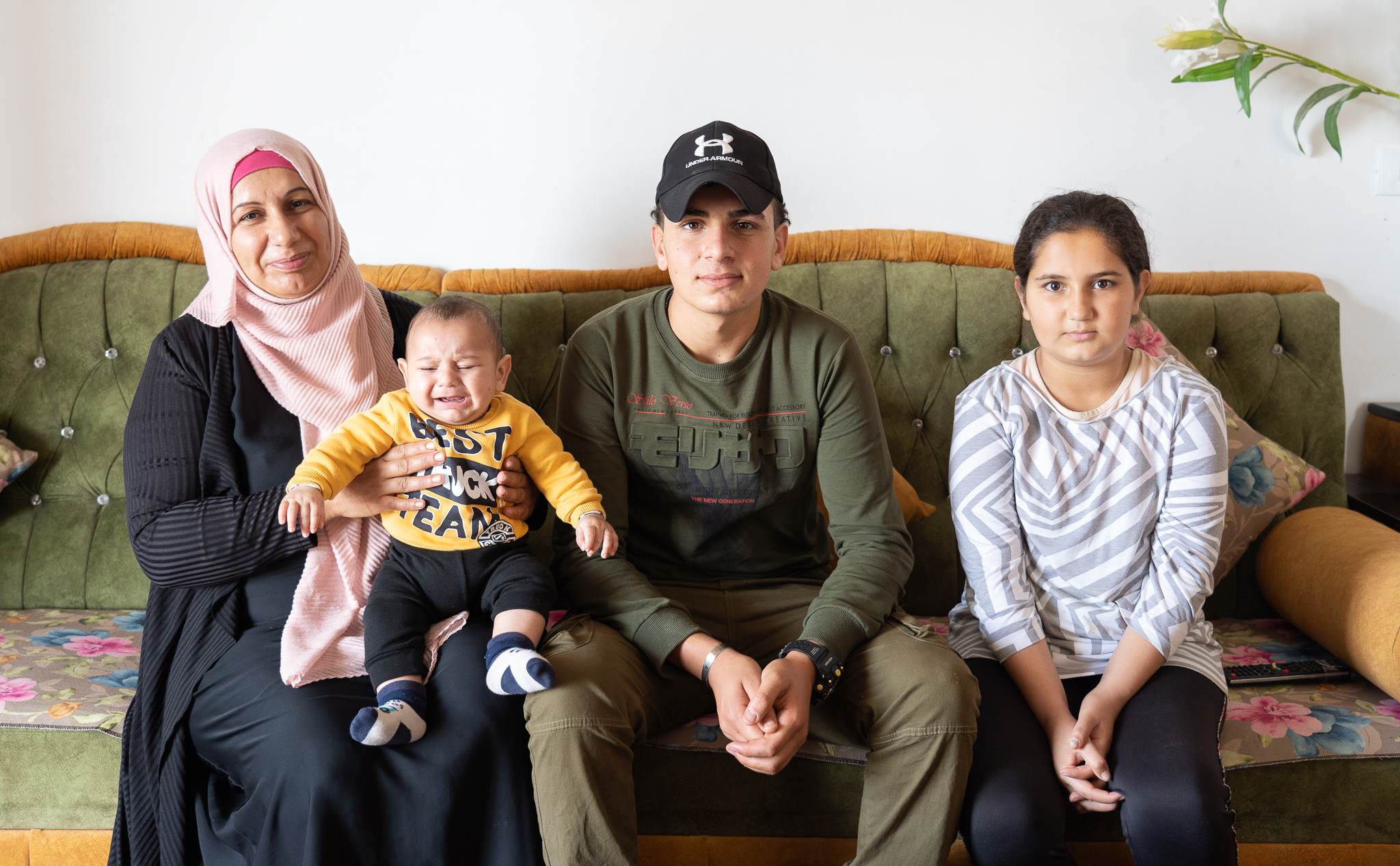 Ismail sits with his mother, baby brother, and younger sister at their home in Beit Fajjar after his release from detention. (Photo: DCIP)