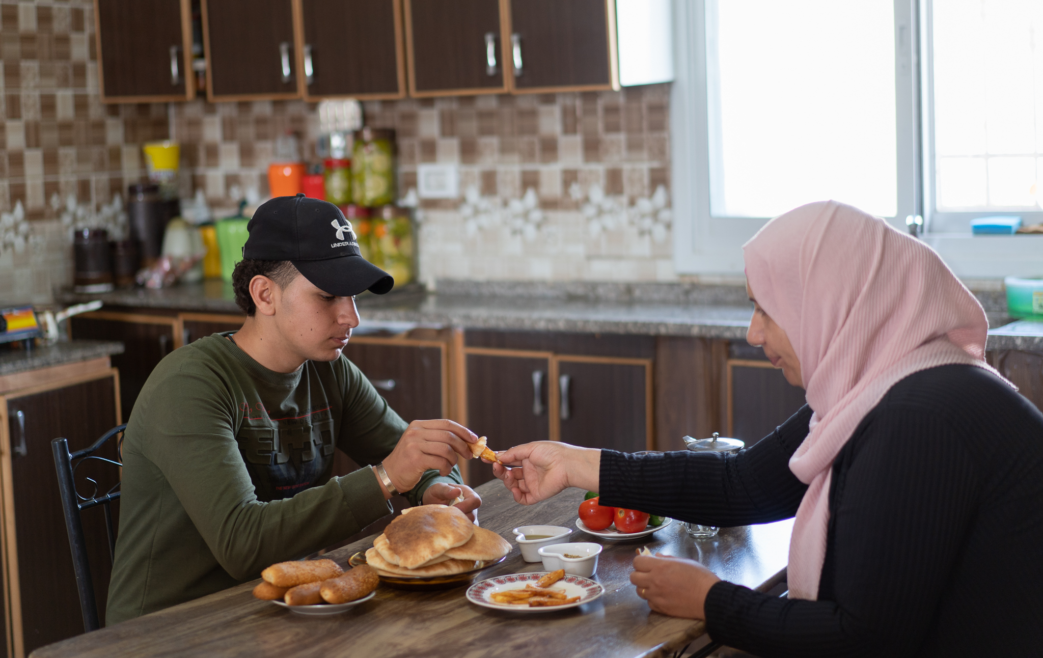 Ismail shares a meal with his mother at their home in Beit Fajjar in the occupied West Bank. (Photo: DCIP)