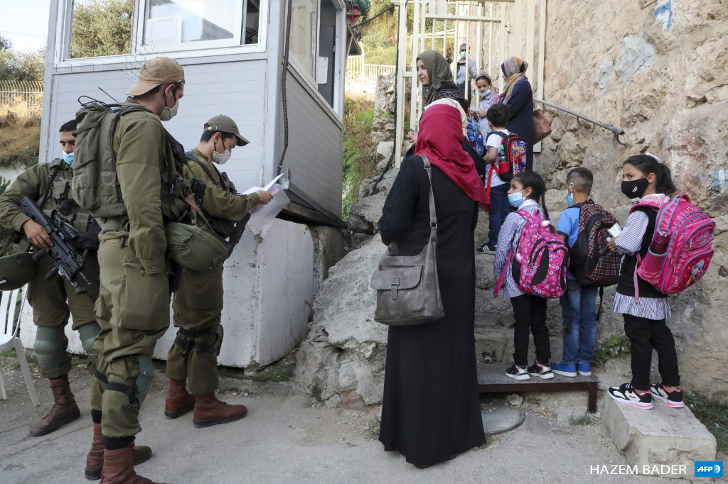 Palestinian students and teachers wait for Israeli soldiers to allow them to cross a military checkpoint near the Jewish settlement of Beit Hadasa in the occupied West Bank city of Hebron on September 6, 2020, as they go to school for the first day of classes. (Photo: AFP / Hazem Bader)