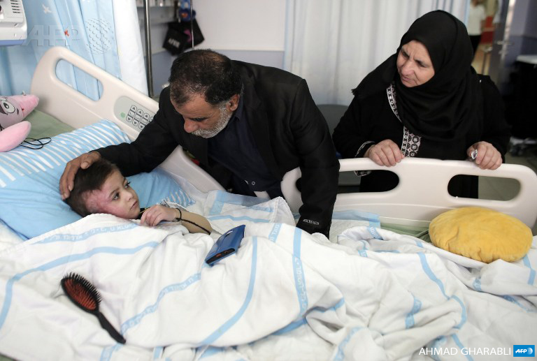Four-year-old Ahmed Dawabsha receives a visit from his grandparents at the Tel Hashomer hospital on December 5, 2015, in Ramat Gan near the Israeli city of Tel Aviv, where he was being treated for burns after his family house was firebombed by Jewish extremists on July 31, in the Israeli-occupied West Bank village of Duma. (Photo: AFP / Ahmad Gharabli)
