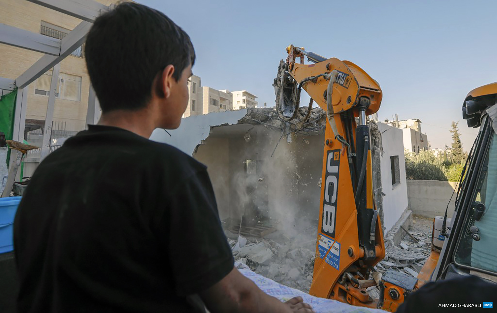A Palestinian boy watches as an excavator hired by his family demolishes their family home in the Al-Tur neighborhood of East Jerusalem on July 2, 2020. (Photo: AFP / Ahmad Gharabli)