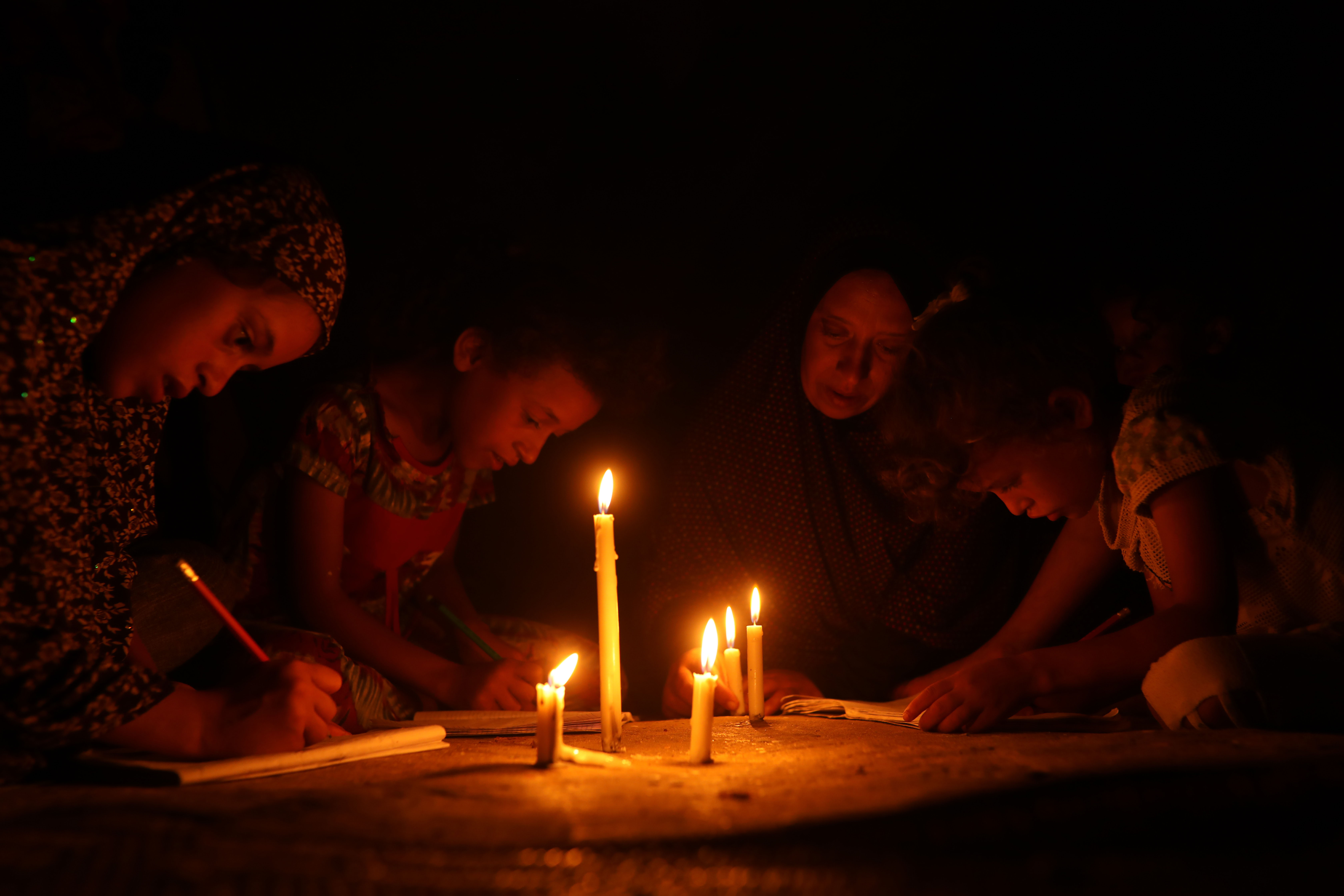Palestinian children use a gas lamp and candles to do their homework at their home in Khan Yunis in the southern Gaza Strip on August 19, 2020. (Photo: Activestills / Mohammed Zaanoun)