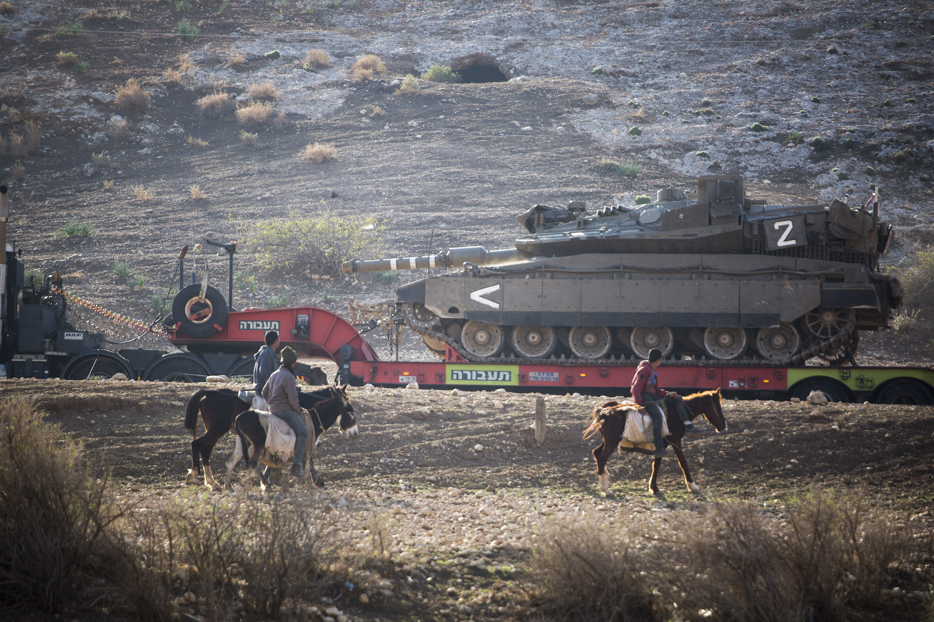 Palestinian youth look at an Israeli transporter, carrying an army tank, during an Israeli military training in the northern Jordan valley in the occupied West Bank. (Photo: Activestills / Keren Manor)