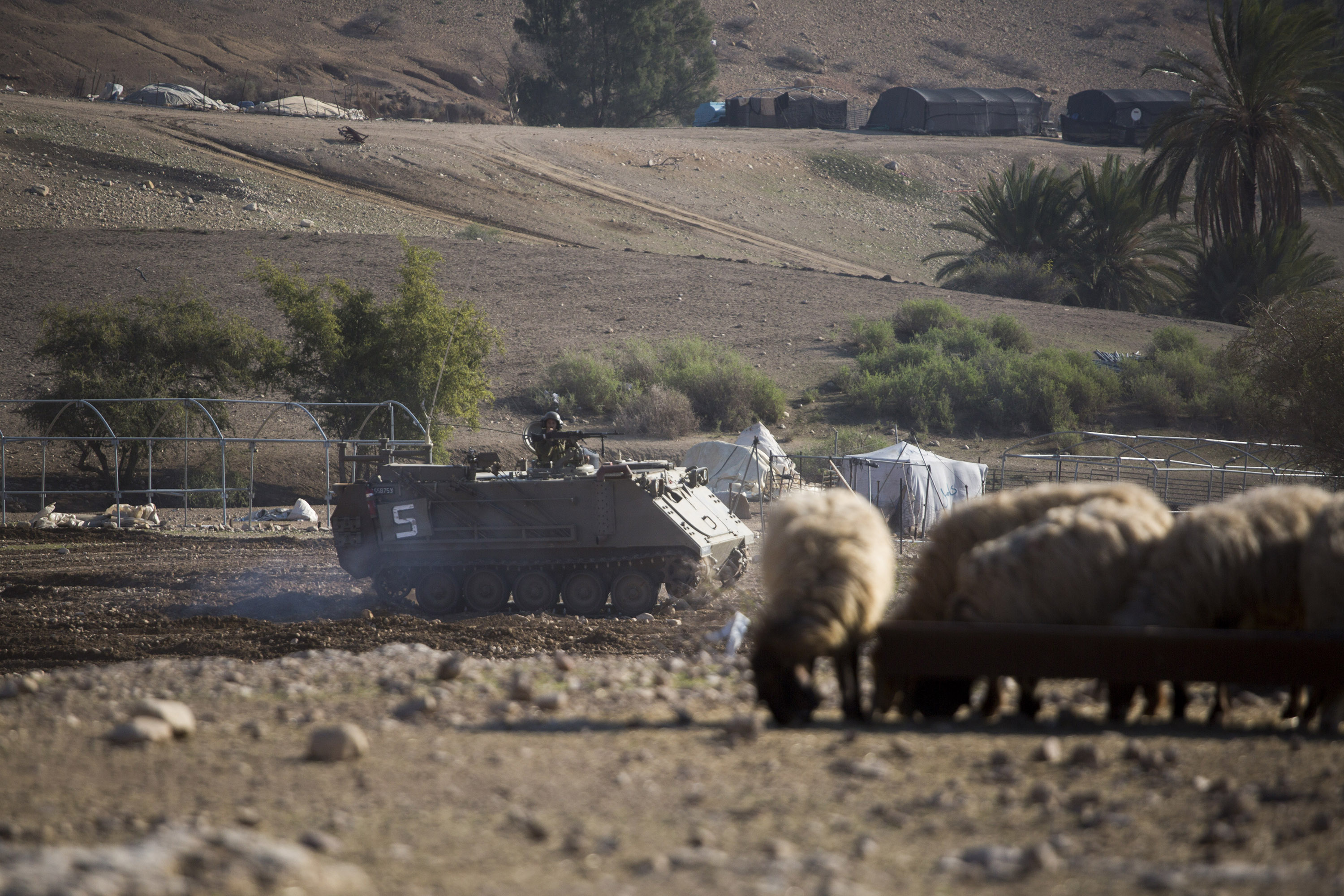 An Israeli army vehicle passes next to a Palestinian family compound during an Israeli military training in the northern Jordan valley in the occupied West Bank. (Photo: Activestills / Keren Manor)