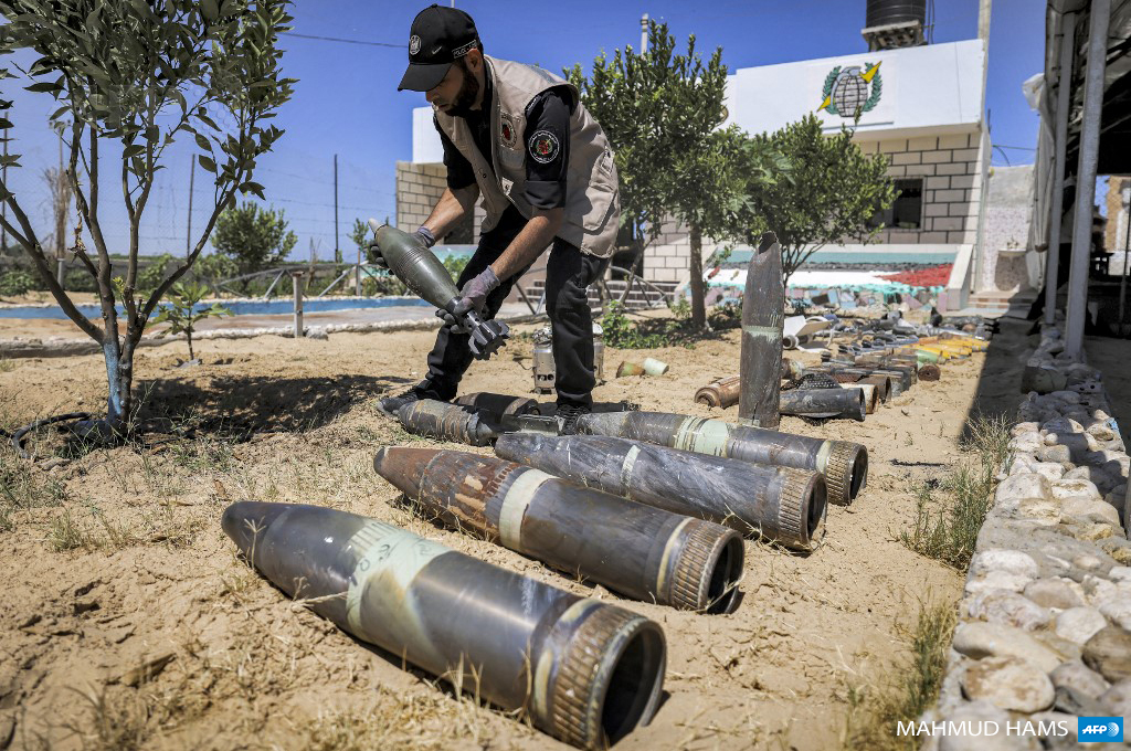 A Palestinian explosives expert lays out unexploded ordnance at a local police precinct in Khan Yunis in the southern Gaza Strip on June 5, 2021 following the 11-day Israeli military offensive on the Gaza Strip during May 2021. (Photo by Mahmud Hams / AFP)