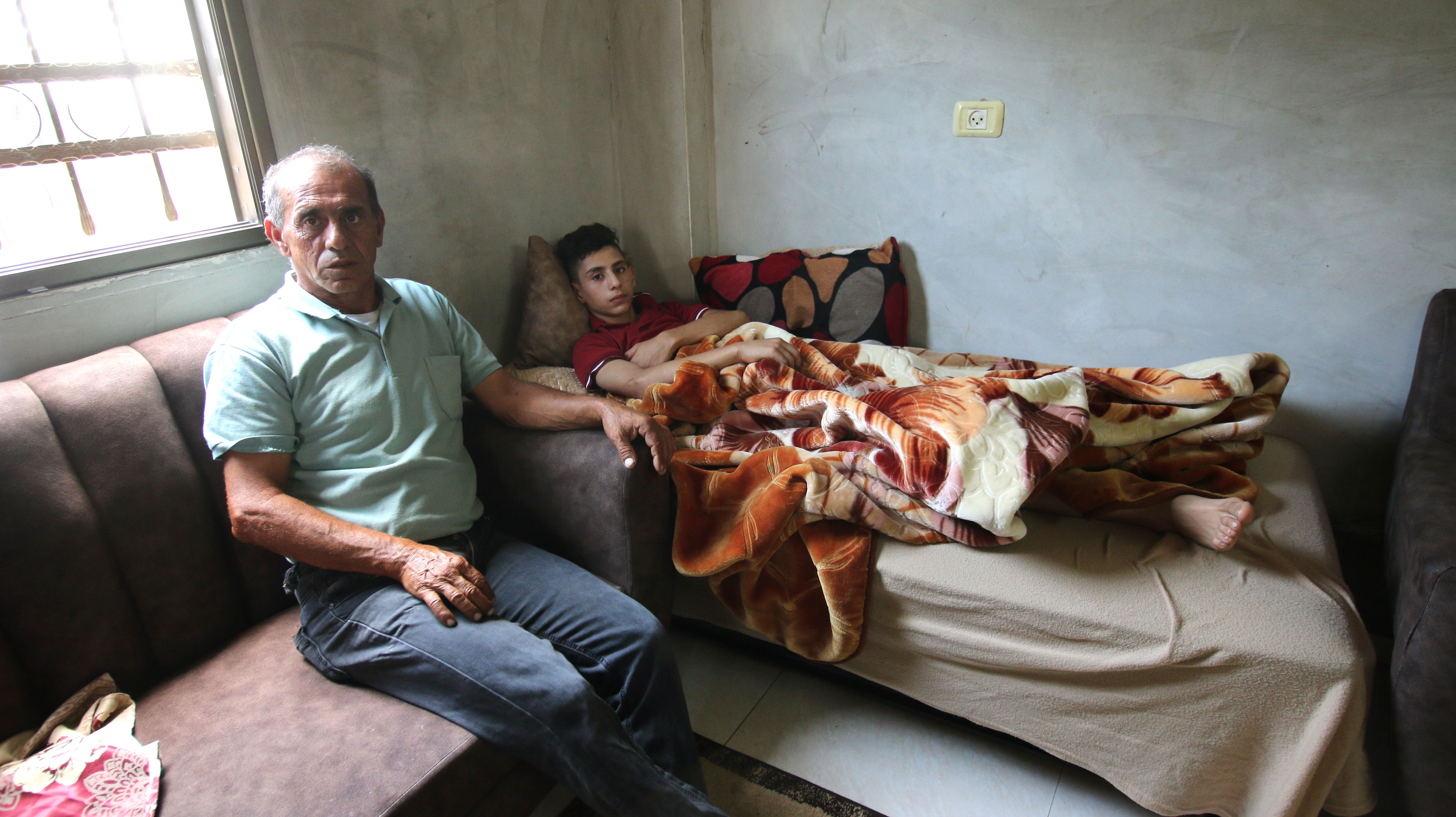Tareq Z., 15, remains unable to walk after he was attacked by settlers in Homesh south of Jenin on August 17. His father, Abdurrazaq sits next to him in their home in Silat Ad-Dhaher. (Photo credit: DCIP / Ahmad Al-Bazz)
