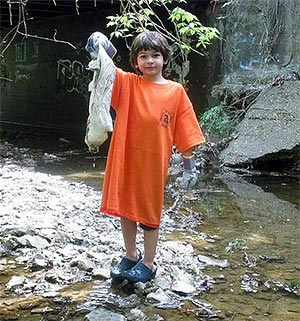 Boy holding up trash he removed from creek