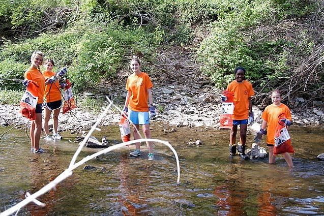 High School students remove trash from the creek