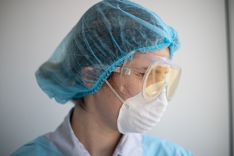 female medical worker wearing protective gear, facemask and goggles