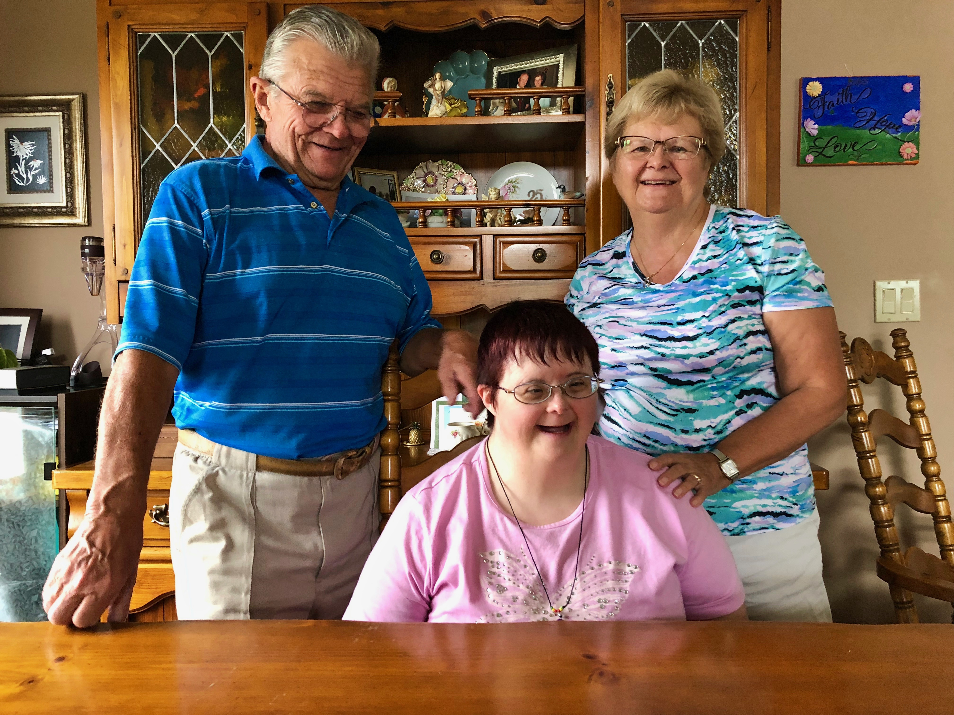 Greg and Lois Bebbington stand behind their daughter Stacy in their dining room.