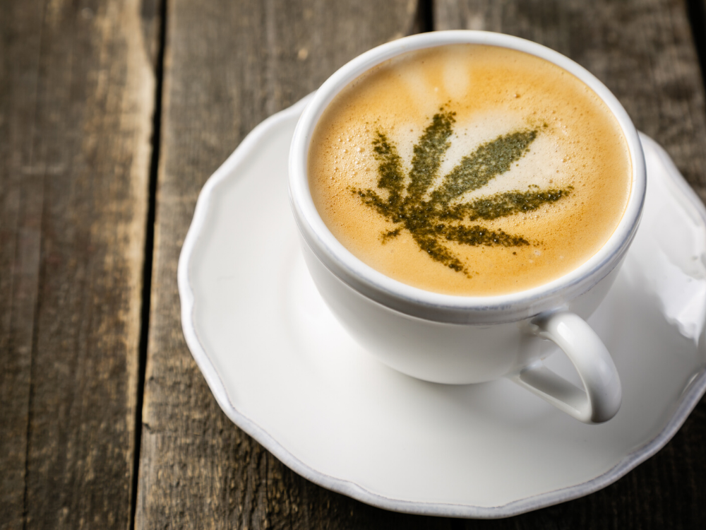 A cannabis leaf is seen atop a cup of coffee