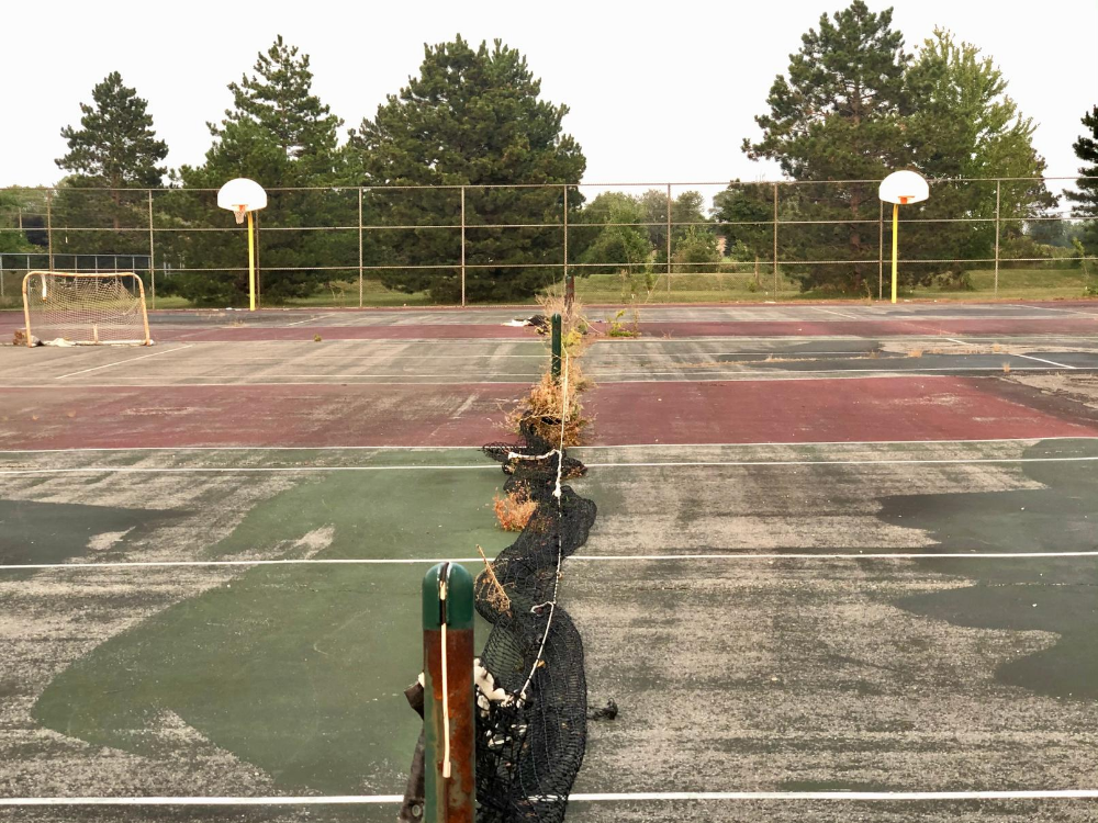 The dilapidated tennis courts at St. Thomas of Villanova High School