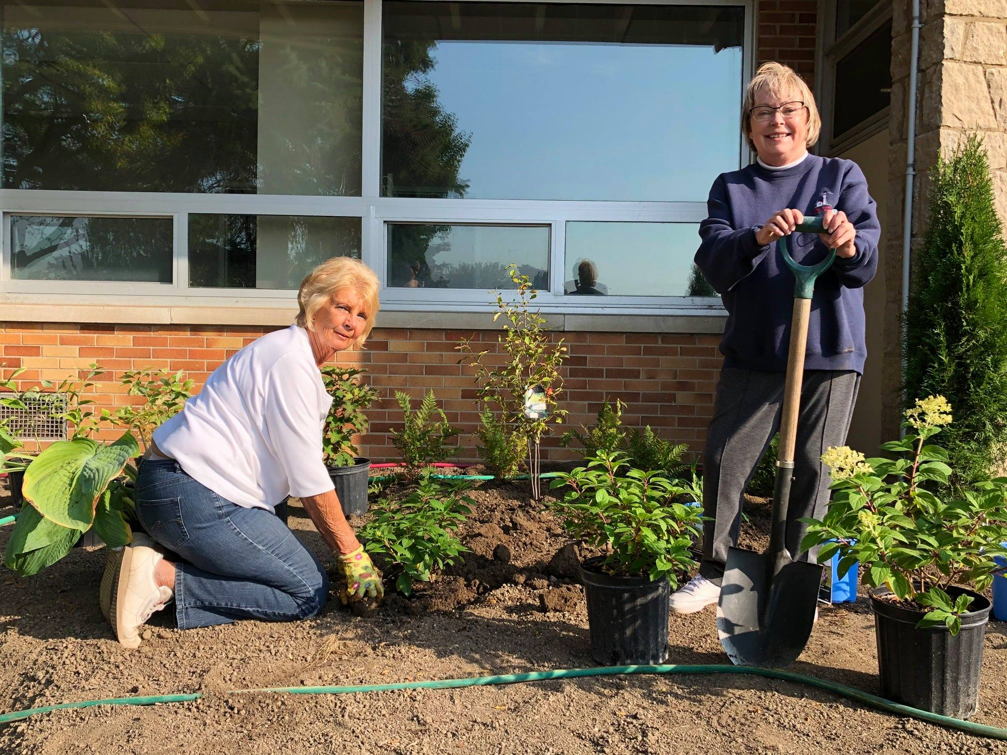 Members of Amherstburg's Fort Malden Horticultural Society work on their Signature Garden outside the community hub.