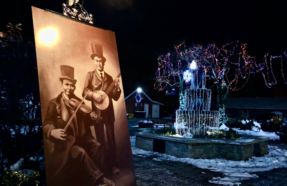 Two historic figures on a River Lights sign in front of a lit fountain in King's Navy Yard Park.