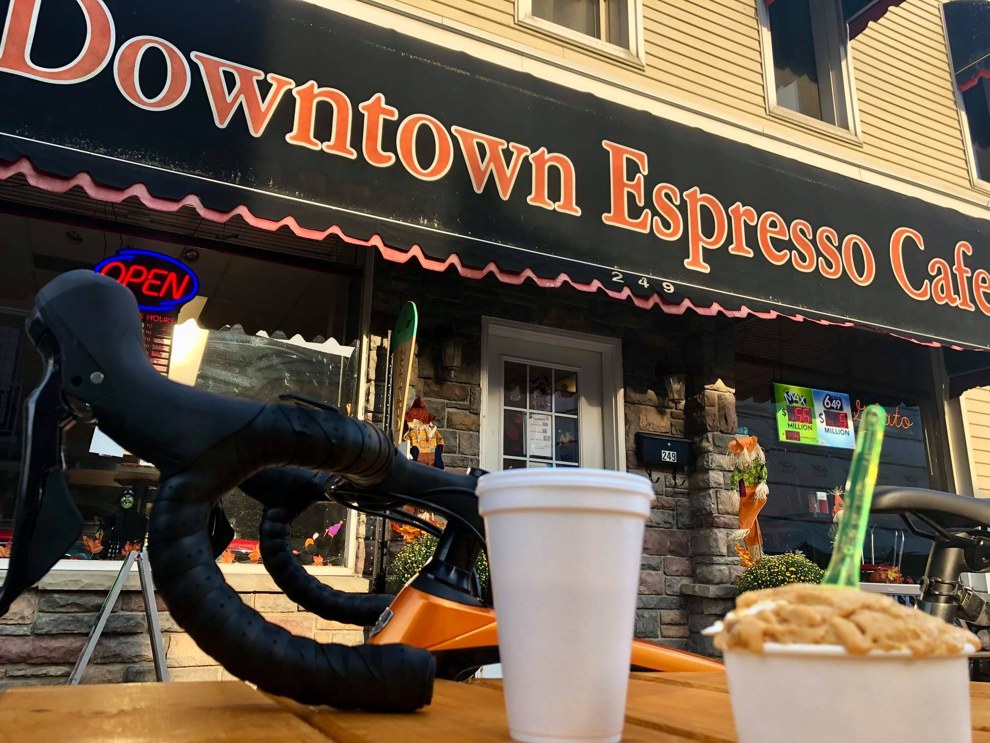 A cup of espresso and gelato on a picnic table in front of a bicycle and Downtown Espresso Cafe in Amherstburg
