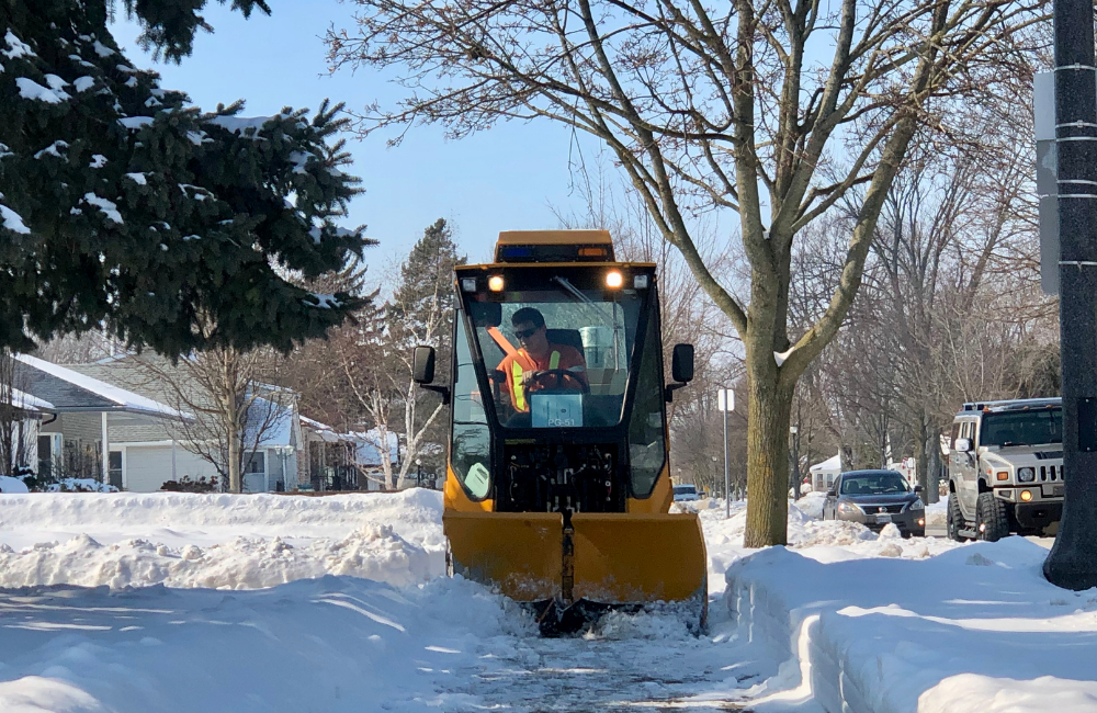 A snow plow operator clears a sidewalk on Alma Street in Amherstburg