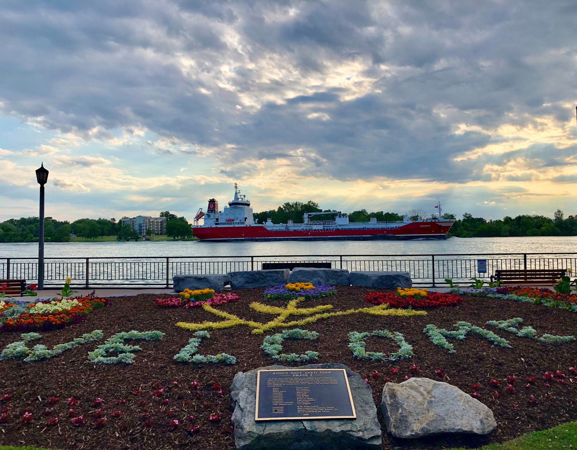 A boat cruises on the Detroit River and in the foreground it spells Welcome in a garden.