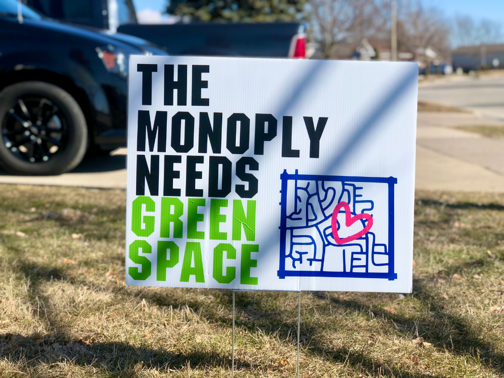 A sign reading Monopoly Needs Its Greenspace