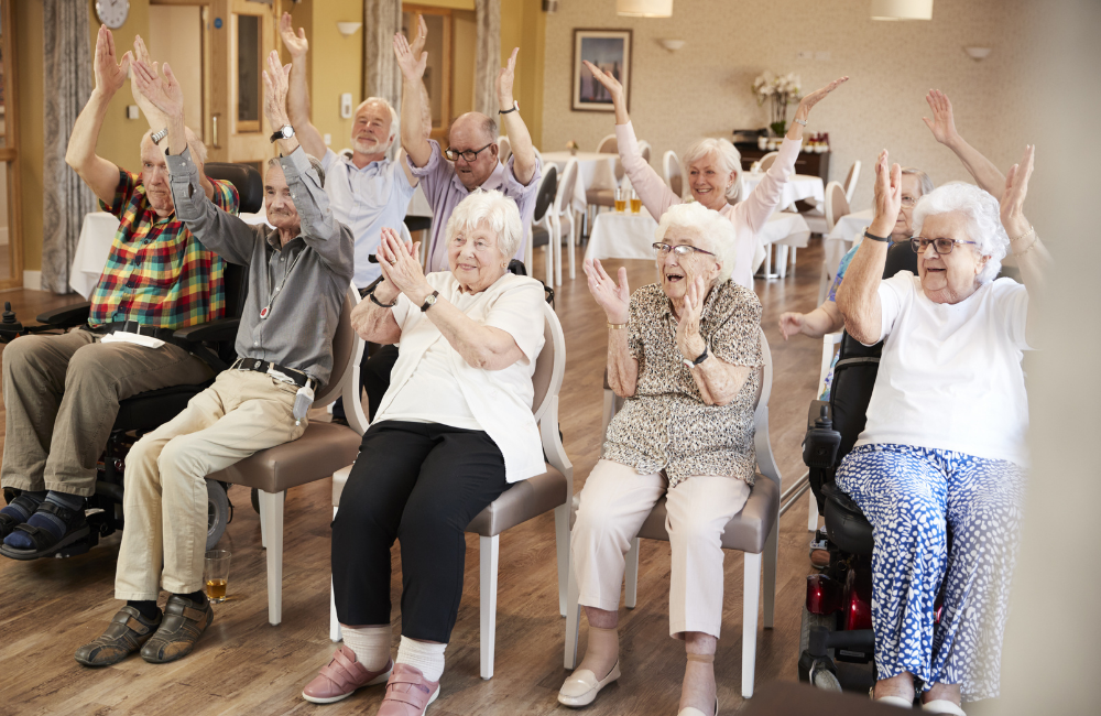 A group of seniors smile with their hands in the air while doing exercises.