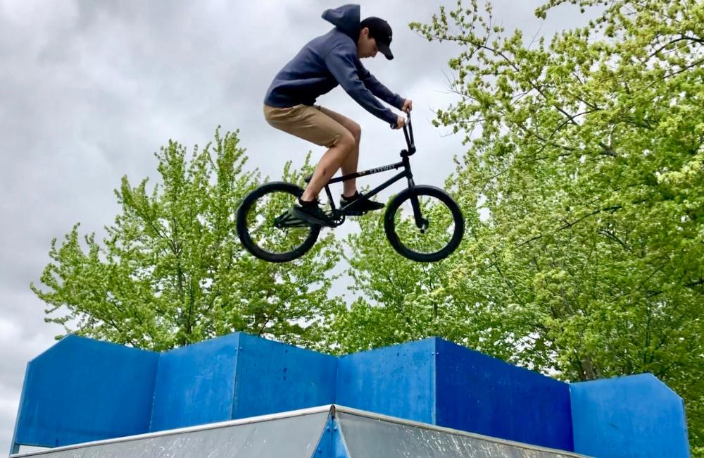 A cyclist catches huge air off a blue skateboard ramp!