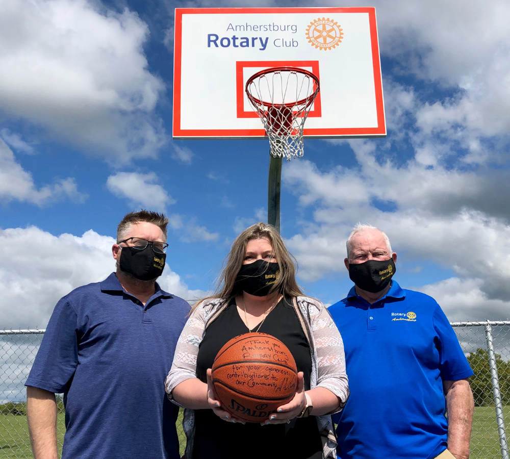 Rotary Club of Amherstburg members hold a basketball on the court in Anderdon
