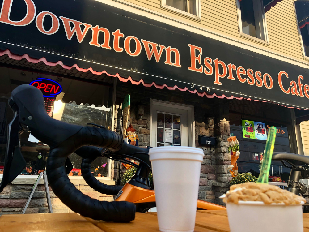 A bike helmet and coffee on the table in front of Downtown Espresso Cafe