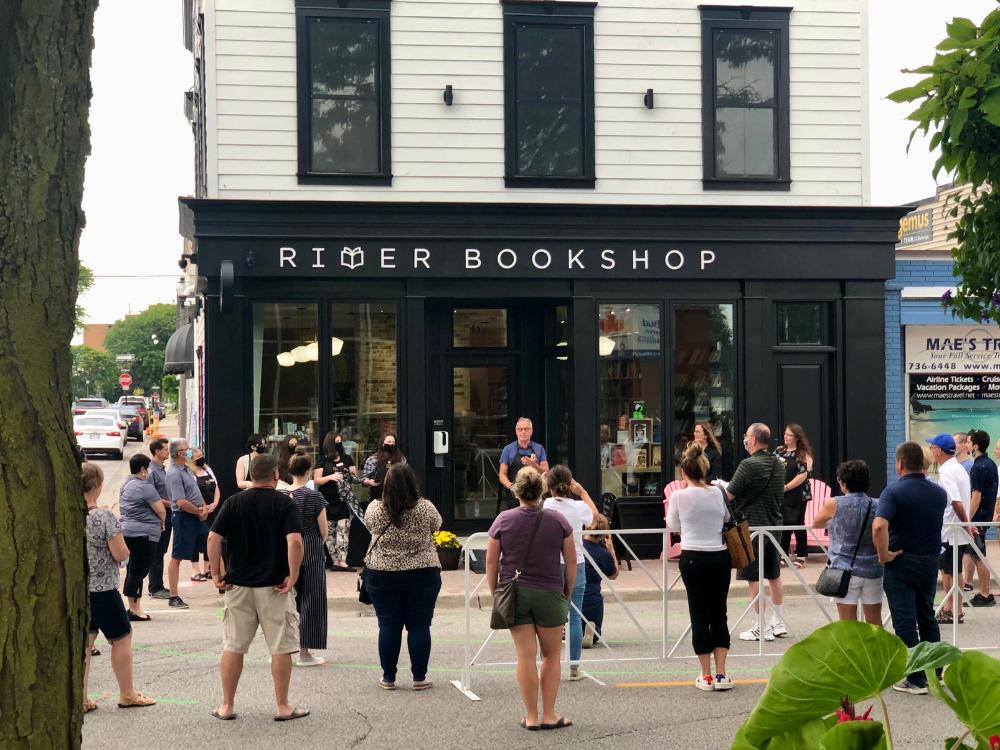 A crowd listens to Richard Peddie speak outside River Bookshop in Amherstburg.