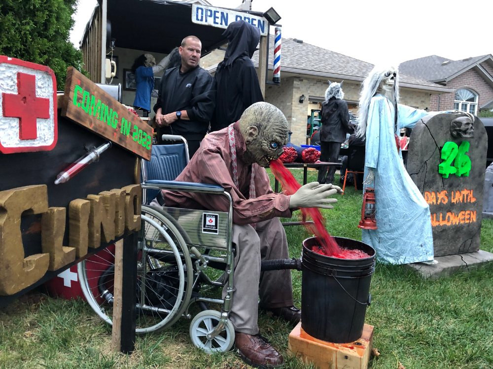 Ken Grant watches as his Halloween monster vomits into a bucker