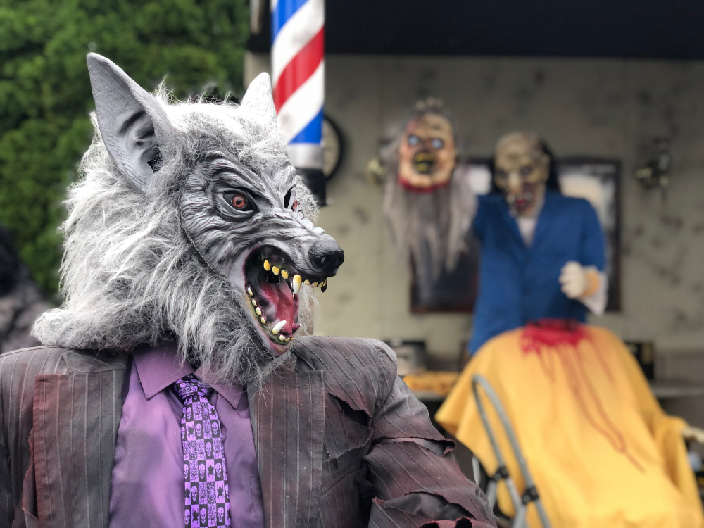 A werewolf with a monster holding a severed head in the background