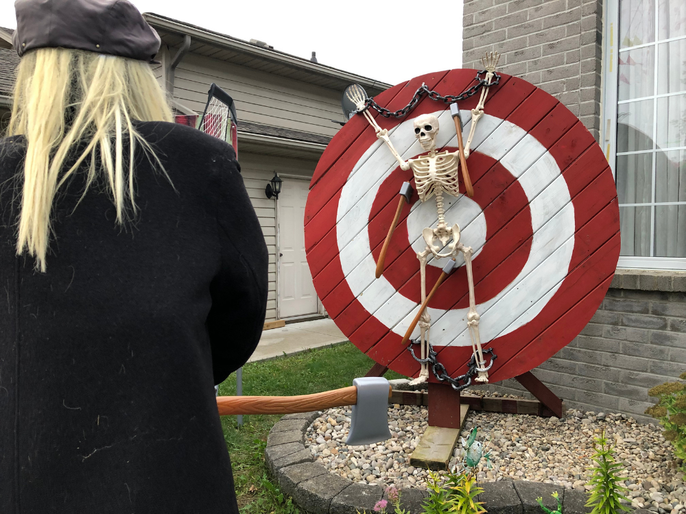 A skeleton chained to a target with a monster ready to throw an axe