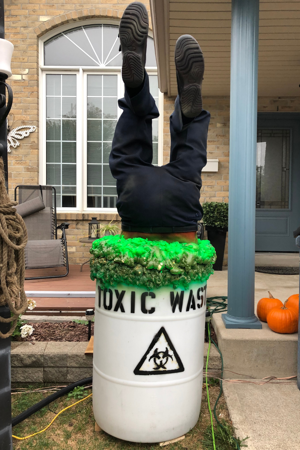 Legs stick out from a bin marked Toxic Waste