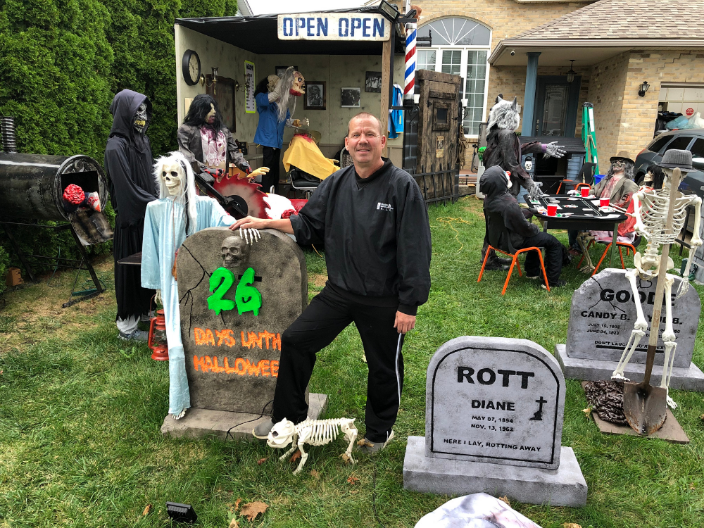 Ken Grant in his haunted yard with a sign indicating its 26 days until Halloween