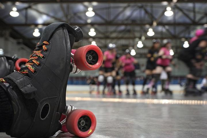 An old school black roller skate with red wheels