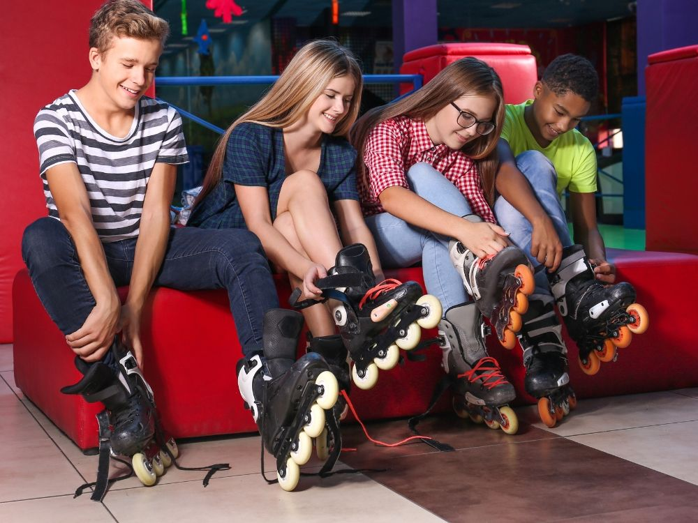 Four teens sitting down tying up their inline skates