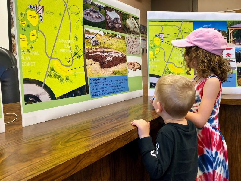 Two kids check out concept drawings for a revitalized Beaudoin Park in River Canard